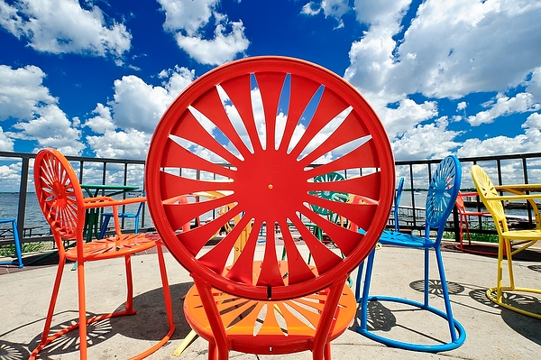 Puffy white cumulus clouds and a deep blue sky make for a striking view of Memorial Union Terrace chairs at the University of Wisconsin-Madison.