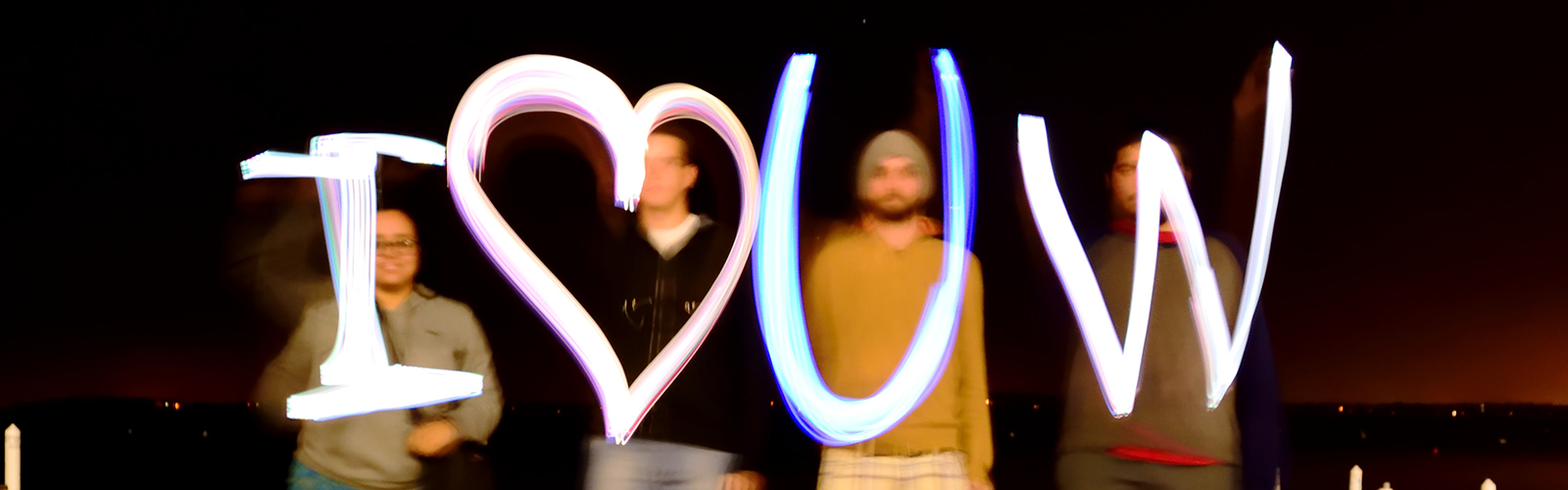 Four VISP alumni spell out 'I love UW' in glow lights in long exposure photo taken with dark lake as background.