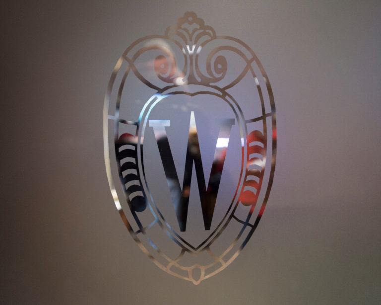 A relief of W Crest graphic is pictured in a frosted-glass door leading to one of the suite boxes at Camp Randall Stadium at the University of Wisconsin-Madison on Nov. 15, 2014.