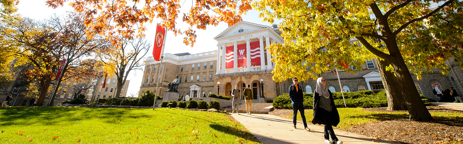 Students walk along a colorful tree-lined sidewalk outside Bascom Hall in fall at the University of Wisconsin-Madison on Nov. 4, 2016.