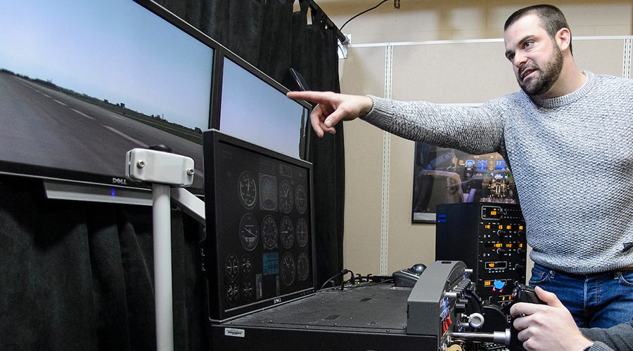 Student sits in front of flight simulator with instructor offering guidance.